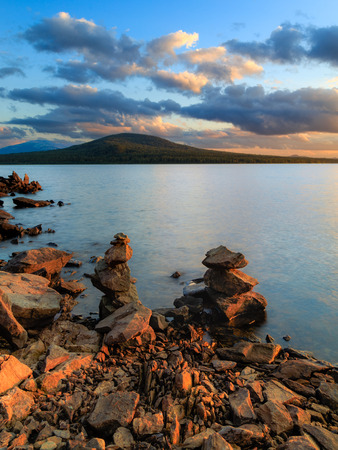 water stone: sunset on the lake, stones in water, stone coast on a lake Stock Photo