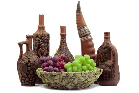 Wine jars-bottles of clay with wine and grapes in front photo