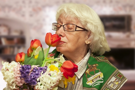 Grandmother with flowers on a blurry room background photo