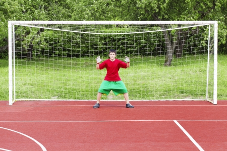 Boy standing in football goal Stock Photo