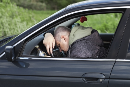 Drunk man asleep at the wheel photo
