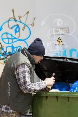 Tramp digging in dumpster Stock Photo - 14030227