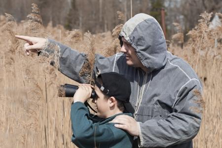 Vater und Sohn beobachten die Vögel am See Standard-Bild - 14101745