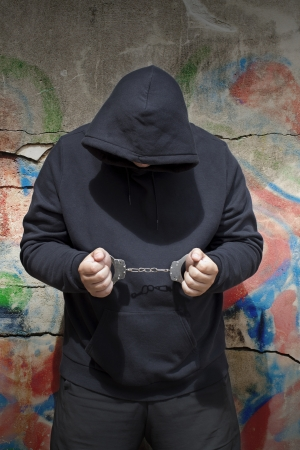 Man in handcuffs on a wall background with shadows photo