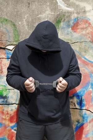 Man in handcuffs on a wall background Stockfoto
