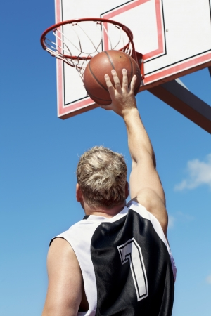 Basketball player throws ball in the basket photo