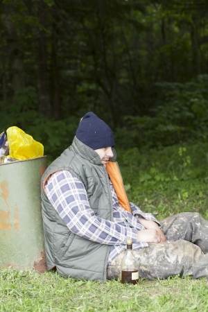 Homeless leaning against the garbage bins Stockfoto