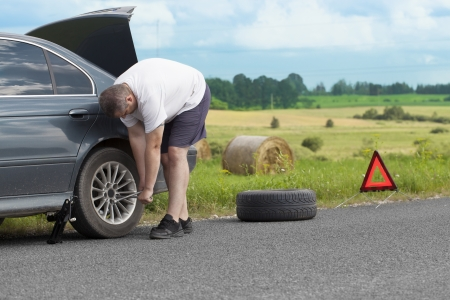 Man changing tire on the road photo