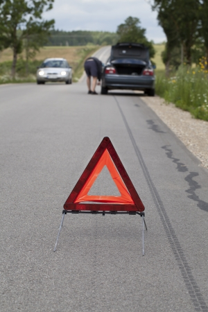 Warning triangle on the road before car photo