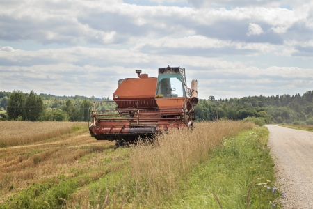 Old harvester on the field near road photo