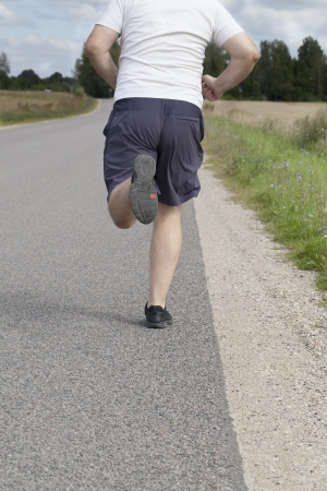 Fat man running on a rural road Stock Photo