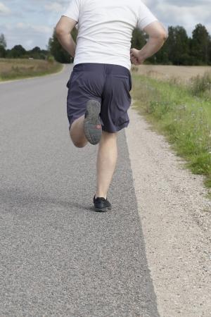 Fat man running on a rural road Фото со стока