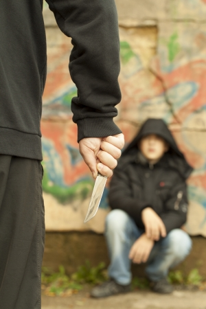 Boy looks at a man with a knife Banco de Imagens