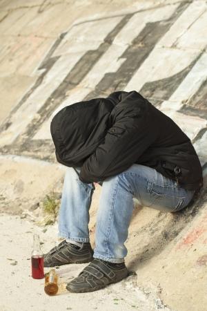 alcoholic: Boy sleeping under a bridge with two drink bottles near