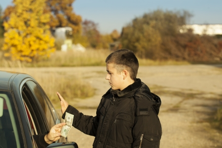Someone from the car is offering money to the boy
