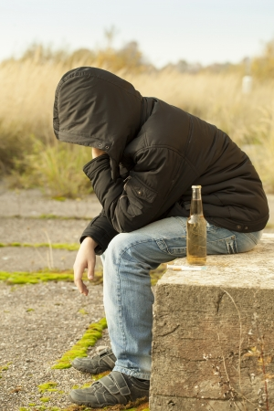 heartache: Boy with a bottle of drink, cigarettes and syringe in the foreground Stock Photo