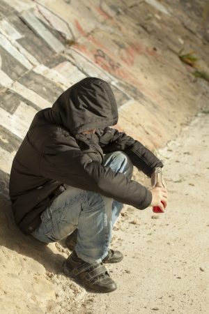 Boy with a bottle of hands sit on a concrete wall Stockfoto