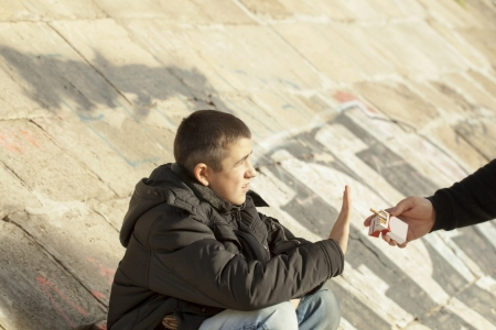 The boy flatly refuse from the offered cigarettes