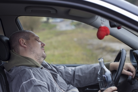 Drunk man asleep in car near highway photo