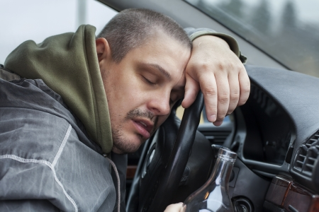 drinking and driving: Drunk man lying on the steering wheel