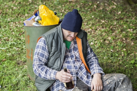 Homeless with botle of drink in hand leaning against garbage bin in the park photo