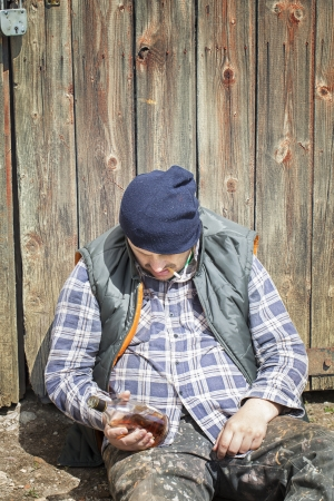 Homeless leaning against barn door photo