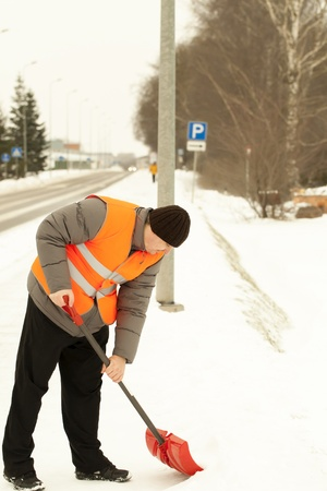 decembe: Man with a snow shovel clean the sidewalk