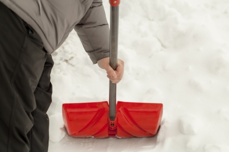 Man with a snow shovel near the snow pile