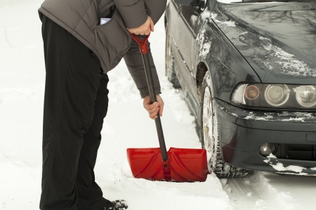 Man with shovel clears snow  around the car Stockfoto