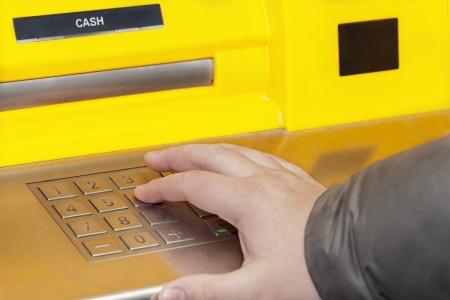 Man s hand near the cash machine on the pin code
