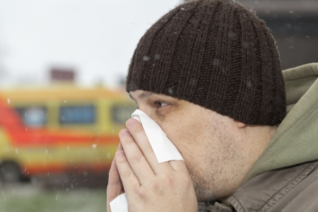 sick day: Man with a runny noise near the hospital
