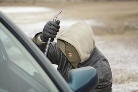 Robber trying to break open the car door Stockfoto