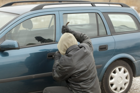 Robber with a crowbar trying to open the car door photo