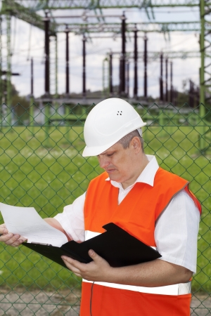 Engineer with folder near the electricity substation Stock Photo - 17625658