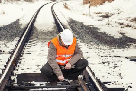 Railroad werknemer met verstelbare sleutel op de spoorlijn Stockfoto - 17753232