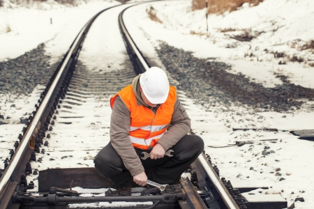 Railroad worker with adjustable wrench on the railroad photo