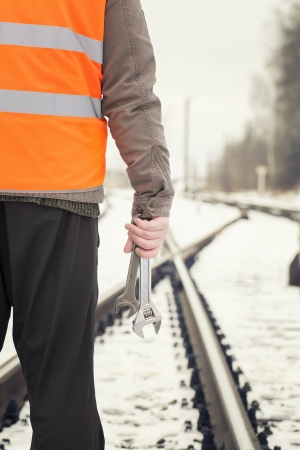 Worker with adjustable wrench in the hands  on railway crossings photo