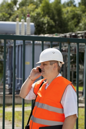Engineer with phone near the electricity substation photo