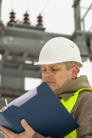 isolators: Engineer with folder on a transformer background Stock Photo