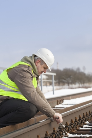 Railroad worker with adjustable wrench fix the nut photo