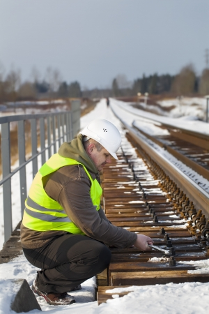 Railroad worker with wrench on the railway bridge photo