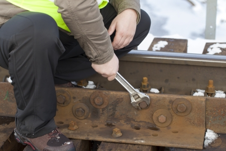 Railroad worker with wrench on the railway bridge fix the nut photo
