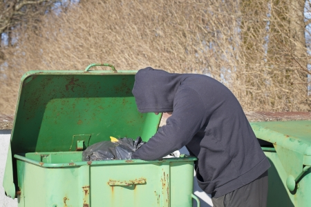 Homeless looking for food in waste containers