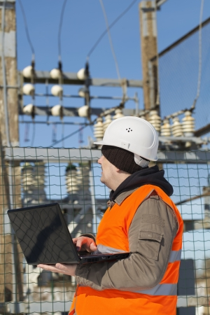 Electrician with computer near the electricity substation