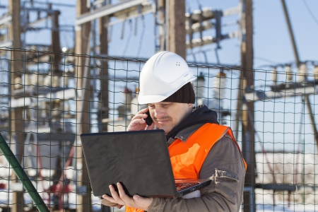 isolators: Electrical engineer with computer near the electricity substation