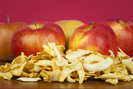Dried apple slices on a table with the fresh apples on the background photo