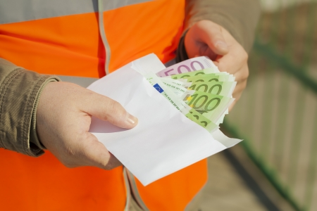 Employee s hands with euro banknotes in envelope