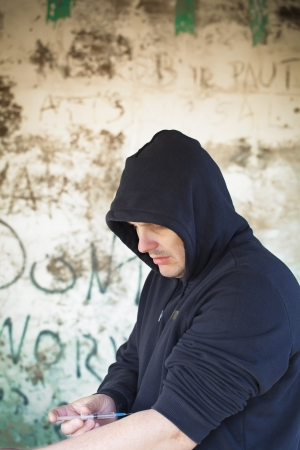 Drug addict man with syringe in hands on a wall background Stock Photo - 19167797