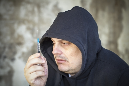 Drug addict men looks at the syringe in the hands Stock Photo - 19202391