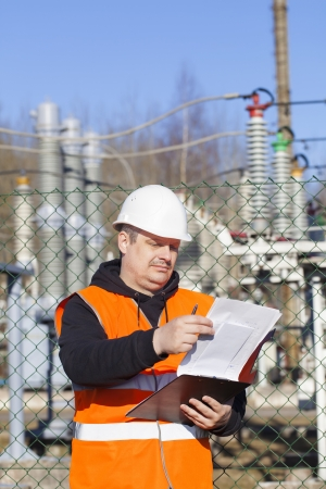 Electrical engineer with documentation near to the electric substations photo